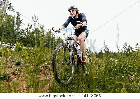 Revda Russia - July 1 2017: female athlete cyclist rides on trail green grass during Regional competitions on mountain bike