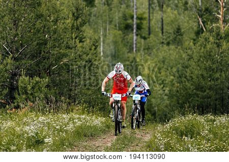 Revda Russia - July 1 2017: two male cyclists riding uphill in forest during Regional competitions on mountain bike