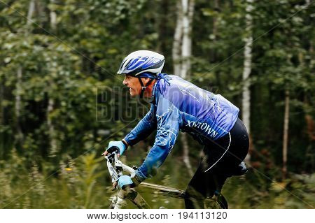 Revda Russia - July 1 2017: close-up middle-aged man cyclist riding in forest during Regional competitions on mountain bike