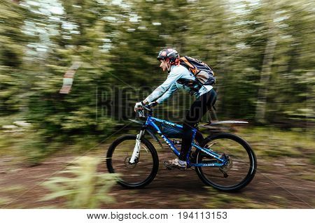Revda Russia - July 1 2017: blurred motion female cyclist rides on trail in woods during Regional competitions on mountain bike