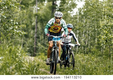 Revda Russia - July 1 2017: male and female athletes cyclists race in forest during Regional competitions on mountain bike