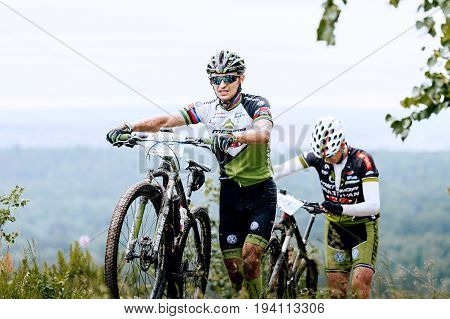 Revda Russia - July 1 2017: two man athlete cyclist walk uphill climbs during Regional competitions on mountain bike