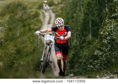 Revda Russia - July 1 2017: man cyclist with mountainbike heavy uphill climbs during Regional competitions on mountain bike