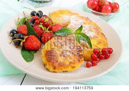 Golden cottage cheese pancakes with fresh berries on a plate on white wooden background. Proper nutrition.
