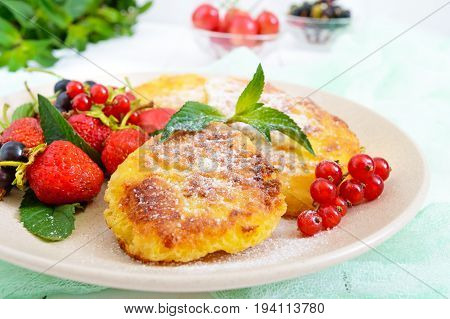 Golden cottage cheese pancakes with fresh berries on a plate on white wooden background. Close up. Proper nutrition.