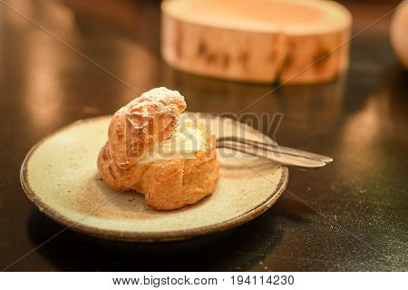 closeup of choux cream with icing on top in ceramic plate on cafe table French dessert choux pastry ball filled with whipped cream