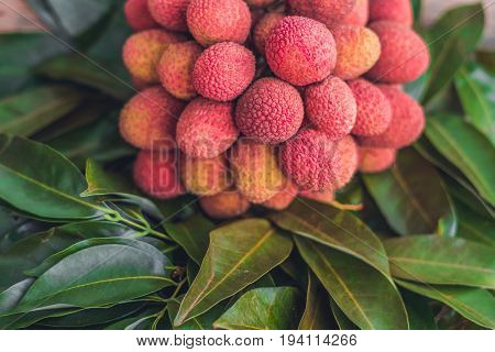 Fresh Organic Lychee Fruit And Lychee Leaves On A Rustic Wooden Background
