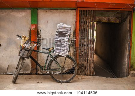 old bicycle with stack of newspapers near rustic wall and opened entrance gate of building urban street scene of Katmandu Nepal