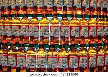 Kiev, Ukraine - January 25, 2013. Close up shot of continuous rows of backlit beer bottles of Budweiser on the round shelves.