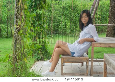 Relaxation Concept : Asian woman sitting on wooden chair at outdoor garden. She relaxing and looking at something with green natural background.