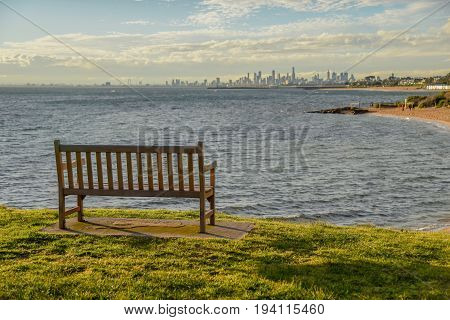 empty wooden bench on green field with beautiful sunset sky near Brighton beach in Melbourne Victoria Australia