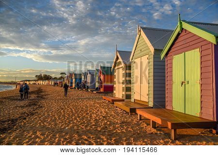 MELBOURNE AUSTRALIA - JULY 18 2016 : Tourists walk on the beach near colorful bathing boxes at Brighton Beach in Melbourne Australia.
