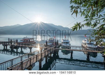 NANTOU TAIWAN - FEBRUARY 13 2017 : travel boats at pier and beautiful sunrise over mountain peak of Sun Moon Lake National Scenic Area popular travel destination in Yuchi Township Nantou Taiwan.