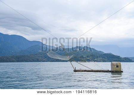 Tranquil scene of Sun Moon Lake with traditional fishing net in Nantou Taiwan