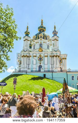 Kiev Ukraine - May 25 2013: View of St Andrew's Church on a hill called Andriyivskyy Descent with many tourists