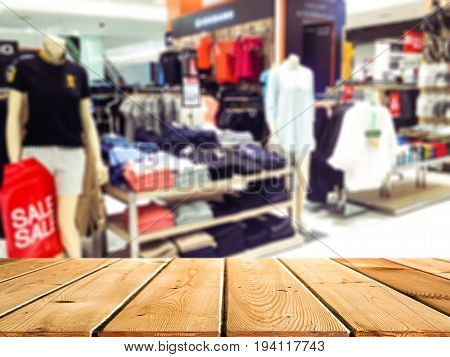 Abstract blur and defocused clothing department in shopping mall and retail store interior for background and empty wooden table space platform for present product.
