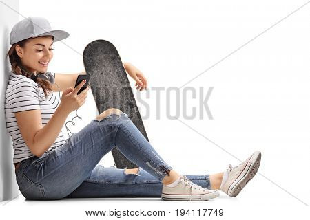 Teenage girl with a skateboard looking at a phone and leaning against a wall isolated on white background