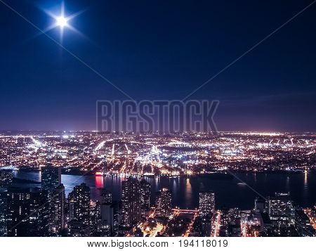 View of night cityscape or skyline of New York City with moon and illuminated buildings and Hudson River from Empire State Building