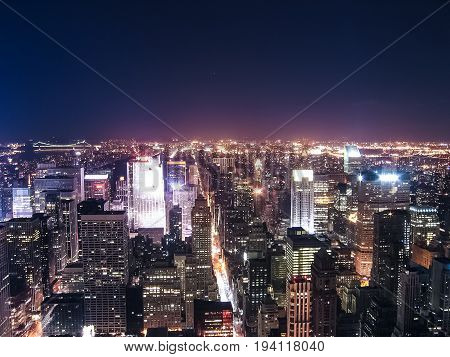 View of night cityscape or skyline of New York City with moon and illuminated buildings from Empire State Building