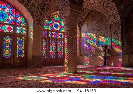 SHIRAZ IRAN - OCTOBER 23 2016 : Unidentified woman traveler photograph the colorful light through stained glass window inside Nasir Al-Mulk (Pink Mosque) a traditional mosque in Shiraz Iran.