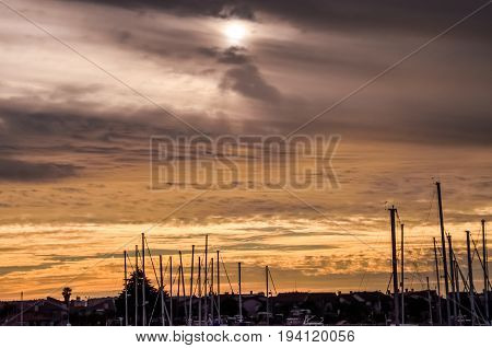 Silhouettes of boats on marina during cloudy yellow sunset in Oxnard California