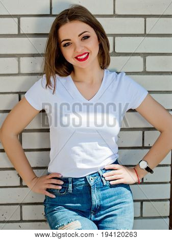 Portrait of a charming girl in a white t-shirt on a white brick wall background. Close-up.
