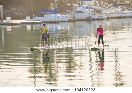 Oxnard USA - March 8 2014: Couple of people paddleboard surfing on calm water on bay in California