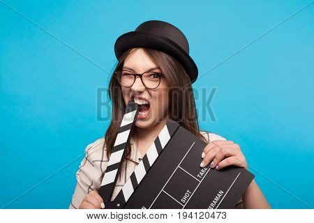 Young woman in hat and glasses biting clapboard and looking at camera on blue background.