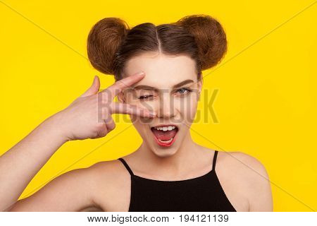 Young girl with nice hairdo posing gesturing with fingers ni studio on yellow background.