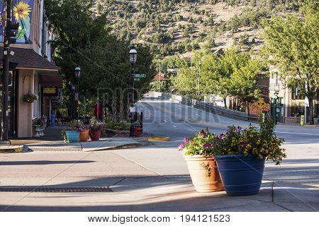 Glenwood Springs USA - September 7 2015: Downtown city with Daily Bread shop flower decorations and main bridge with sidewalk in Colorado