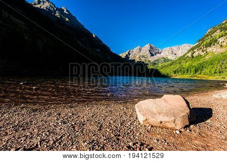 Maroon Bells with large rock boulder in Lake in Fall