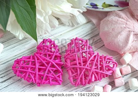 Peonies Flowers Pink Cup Of Tea Rattan Hearts Marshmallow On A White Wooden Background - Stock Image