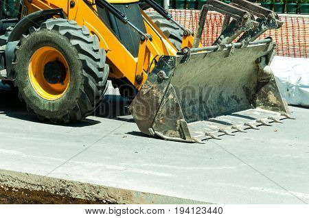 Wheel loader bulldozer excavator construction machinery front side on the street.
