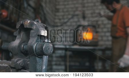 The blacksmith handles the item is removed from the fire, metal bends