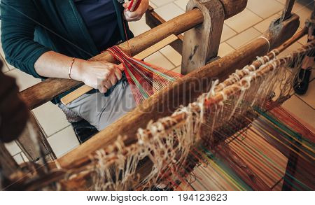 Woman works at old weaving loom. Traditional Russian wooden hand-weaving loom for make cloth, toned