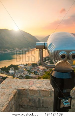 Coin Operated Binocular viewer in Kotor looking out to the Bay and city at sunset time, Montenegro