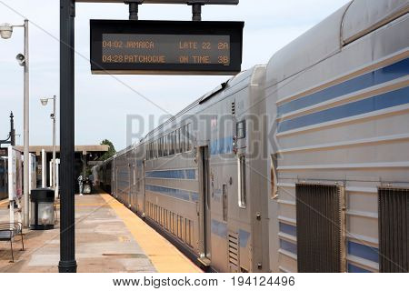 Babylon N.Y. USA - 29 June 2017: Double Decker train sitting on the Babylon platform has to wait for the connecting train from Jamaica which is twenty two minutes late