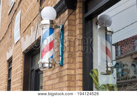 An old fashion Barber Shop Pole on the side of a brown brick building and a reflection of the pole in the window