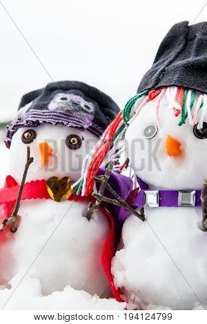 Two stylish snowmen dressed beautifully. Small and cute characters sat in a snow scene in winter during Christmas