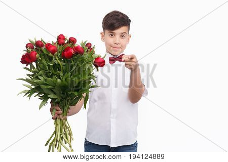 Cheerful elegant boy in shirt and bow tie holding bouquet and pointing at camera.