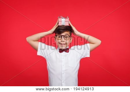 Smiling young boy posing with small giftbox on his head and looking at camera on red background.