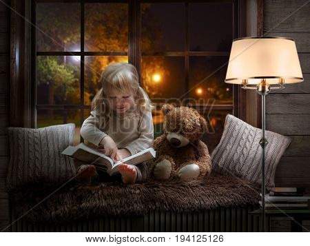 little girl reads a book drives a finger over the lines. The child is sitting with a Teddy bear. Cozy children room beautiful window evening