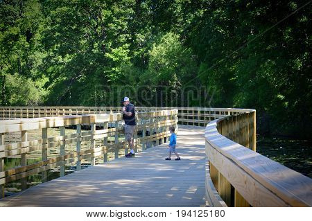 EAGAN, MINNESOTA- JUNE 2017:  A father and son walking on the boardwalk at the park in Eagan, MN.