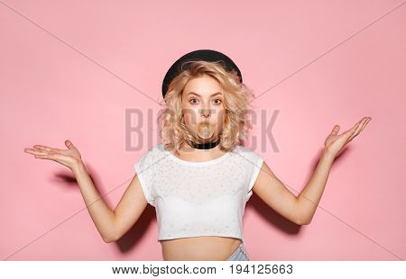 Young expressive girl in stylish clothing blowing bubble from chewing gum and gesturing on pink.