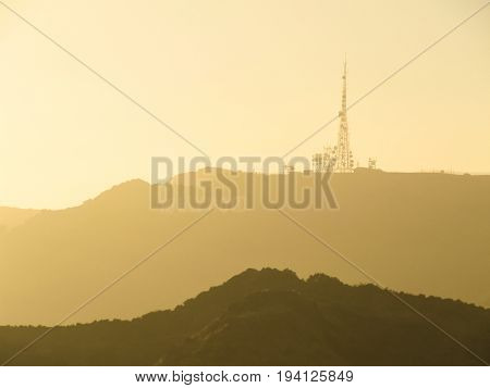 Los Angeles USA - May 24 2010: Hollywood sign on hill during sunrise with soft golden light from Griffith Observatory