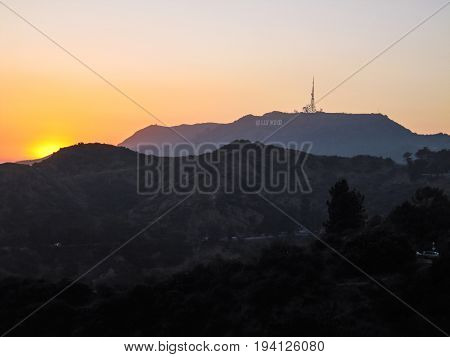 Los Angeles USA - May 24 2010: Hollywood sign on hill during sunset with soft golden light from Griffith Observatory with road and cars