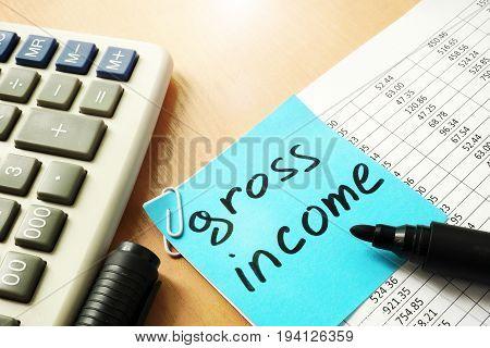 Gross income written on a memo stick.