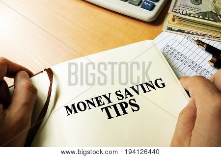 Hands holding book with title money saving tips.