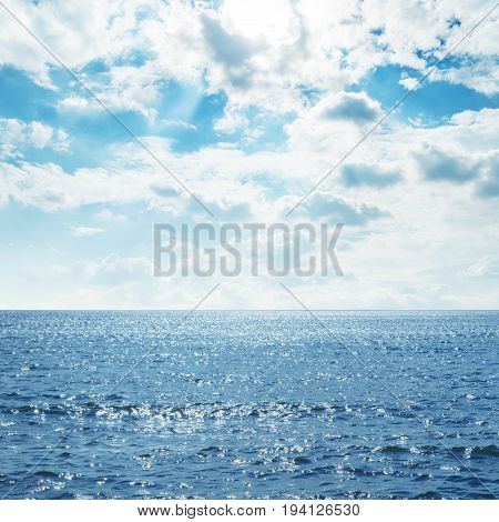 blue sea with waves and clouds over it