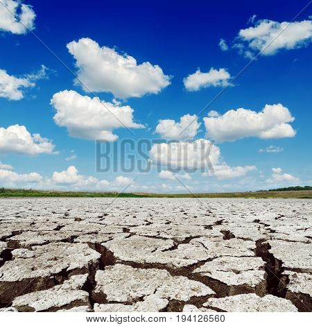 deep blue sky with clouds over drought earth